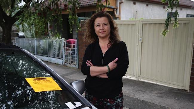 นาง Katrina Gulabovski กับรถโฮลเดนแอสตราสีเงินที่จอดขวางทางเข้าบ้านเธอ : ภาพชั่วคราวจากนสพ. Inner West Courier Inner City