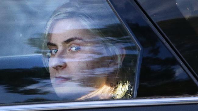 น.ส. Simona Zafirovska ถูกตำรวจจับใส่กุญแจมือนำตัวมาขึ้นรถแล้วขับออกไป : ภาพจากนสพ The Courier Mail