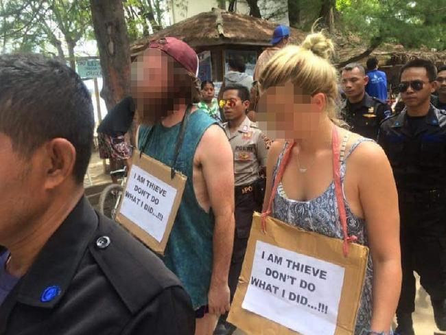 นักท่องเที่ยวชาวออสเตรเลียสองคนถูกป้ายเขียนความกระทำผิดห้อยคอเดินประจานบนเกาะ Trawangan ในประทศอินโดนีเซีย : news.com.au