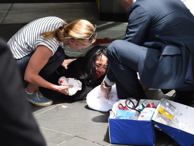 เหยื่อถูกรถชนกำลังได้รับการปฐมพยาบาลจากแพทย์ที่ทำงานอยู่บริเวณที่ใกล้เกิดเหตุ ก่อนหน่วยแพทย์เคลื่อนที่จะมารับหน้าที่นำส่งโรงพยาบาล : ภาพชั่วคราวจากนสพ. Herald Sun