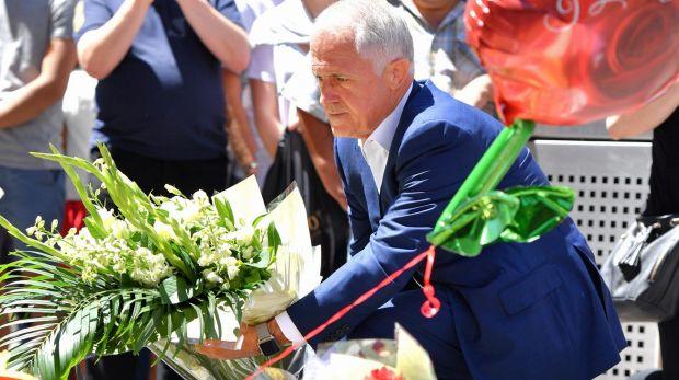 นาย Malcolm Turnbull นายกรัฐมนตรีขณะวางดอกไม้แสดงความไว้อาลัยต่อผู้เสียชีวิตที่บริเวณหน้าไปรษณีย์กลางในนครเมลเบิร์น : ภาพจากนสพ. The Age
