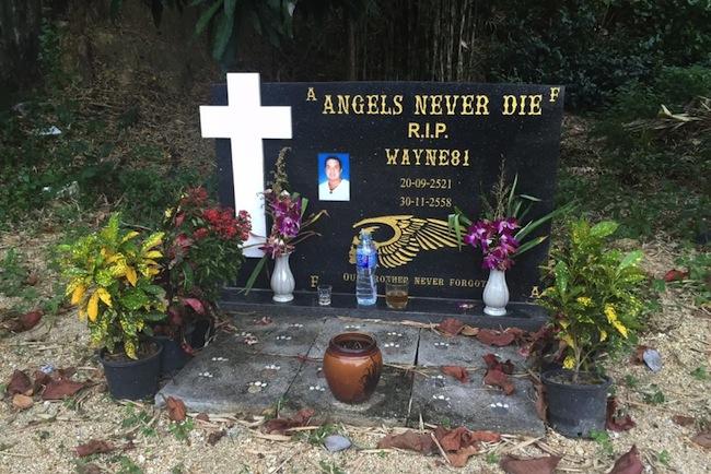 """แผ่นศิลาที่ระลึก (สื่อออสซี่ระบุว่าเป็นศาล) ตรงจุดที่นาย Wayne Schneider เสียชีวิต มีข้อความเขียนว่า """"Angels Never Die"""" และที่ด้านล่างมีตราสัญลักษณ์หัวกะโหลกมีปีกของแก๊งไบกี้ Hells Angels"""