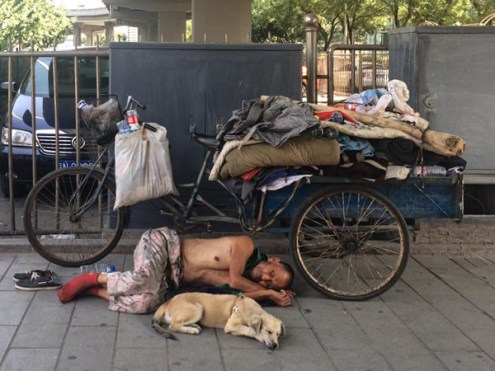 Homeless man and his dog in Beijing city center