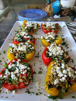 stuffed red and yellow sweet bell peppers, topped with crumbled feta, garnished with chopped parsley, on a long white rectangular platter, with a stack of blue and white plates on a glass coffee table in the living room