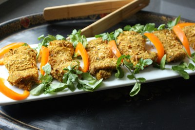 crispy onion chicken, served on a long thin rectangular serving dish, garnished with orange bell pepper and watercress leaves, on a black tray, with wooden serving tongs.
