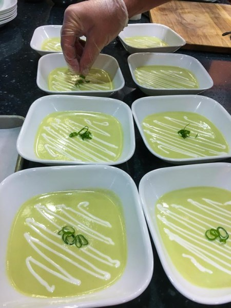 Scallion Soup being Garnished with Creamed Goat Cheese and green part of sliced scallion