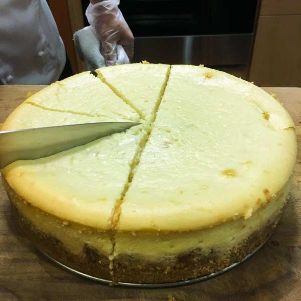 whole cheese cake being sliced