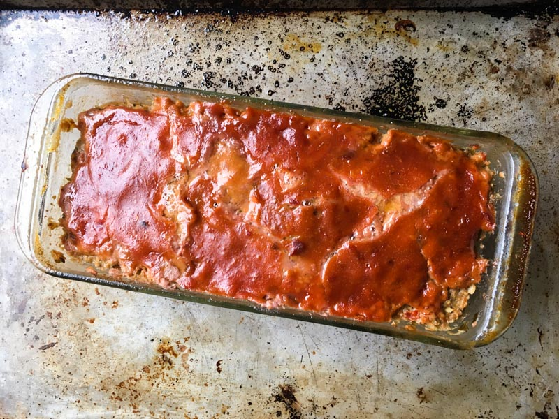 Lamb Meatloaf cooked in a glass loaf pan with Sweet and Spicy Topping on a baking pan
