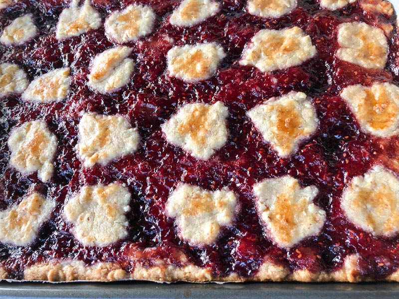 Close up - After cooking Linzer Torte: Browned Torte in 9x13-inch metal baking pan, covered with raspberry jam and dotted with browned puffs of dough resembling clouds.