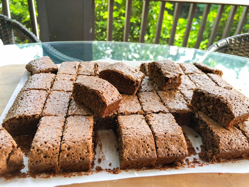 Photo taken outside on a glass table with bishes seen behind the screened in porch. Cooked Espresso Brownies on a wooden board, sliced into 40 portions with some pieces lifted up.