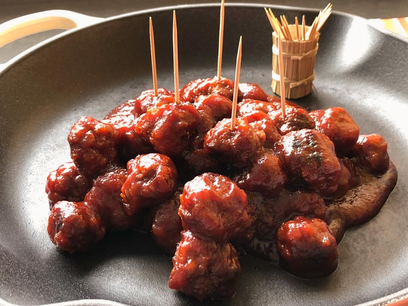 Sweet and Sour Meatballs with toothpicks, ready to serve from a cast iron Le Creuset, off white pan.