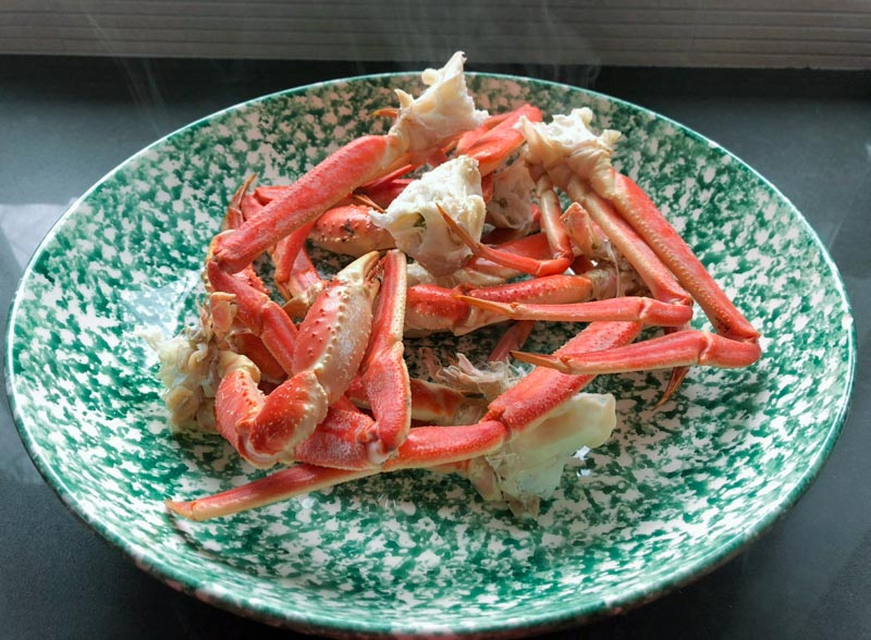 A large green and white bowl with cooked snow crab legs.