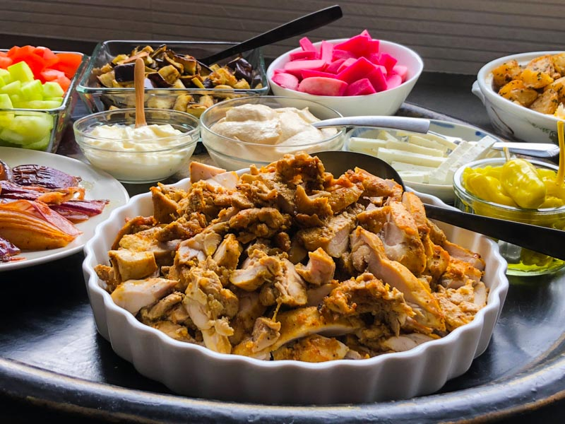 Sam Sifton's Oven-Roasted Chicken Shawarma in a white pyrex dish surrounded by potatoes, rice, roasted vegetables and condiments.