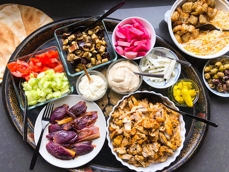 oven-roasted chicken shawarma: Array of dinner items on a tray including marinated oven roasted shawarma chicken, marinated oven-roasted red onion, rice, potatoes, pita bread, roasted aggplant, chopped tomatoes, chopped cucumbers, olives, humus, hot peppers, pickled turnips, olives and garlic mayo