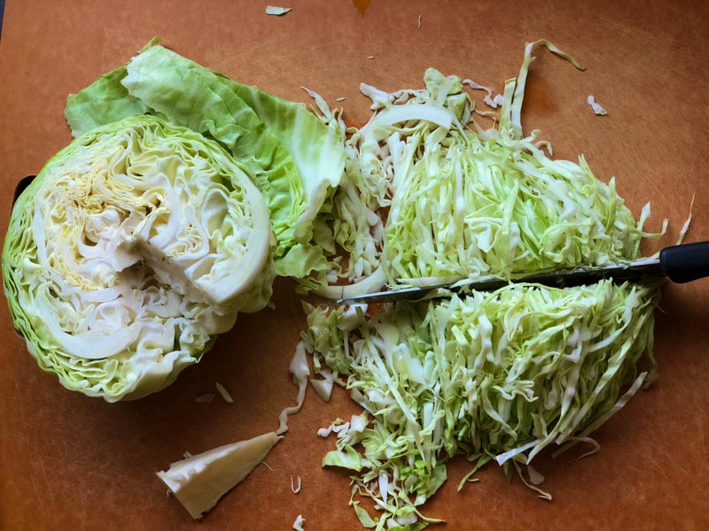 Cabbage being sliced on a cutting board