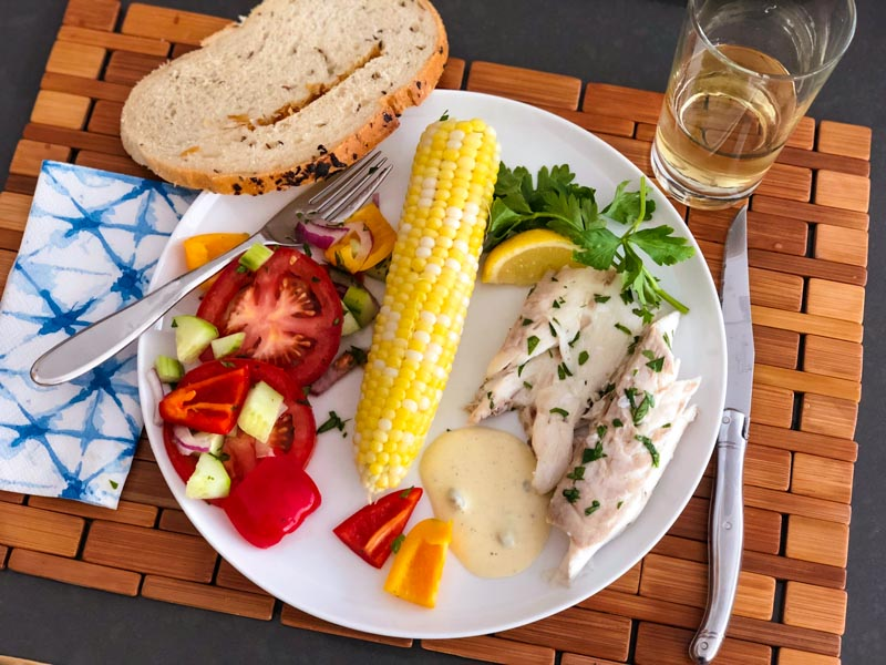 Mediterranean bass in a dinner plate with Dijon Mayonnaise sauce, sweet corn, tomato salad and onion corn bread. Glass of white wine on the side.