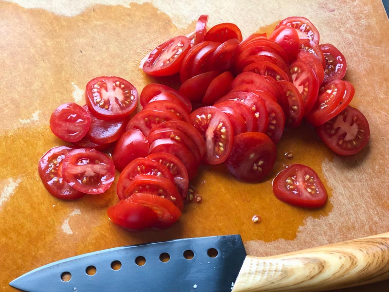 sliced tomatoes on a cutting board with knife