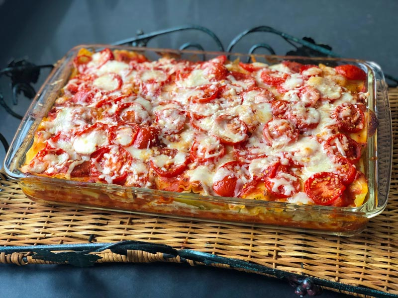 Roasted Veggie Lasagna cooked in a glass lasagna dish, cooling in a tray