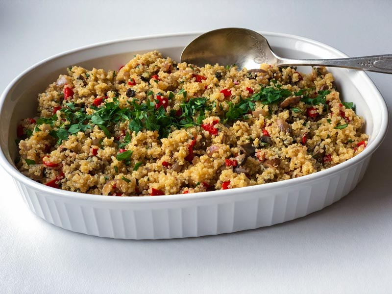 Quinoa pilaf in white casserole with serving spoon on white background