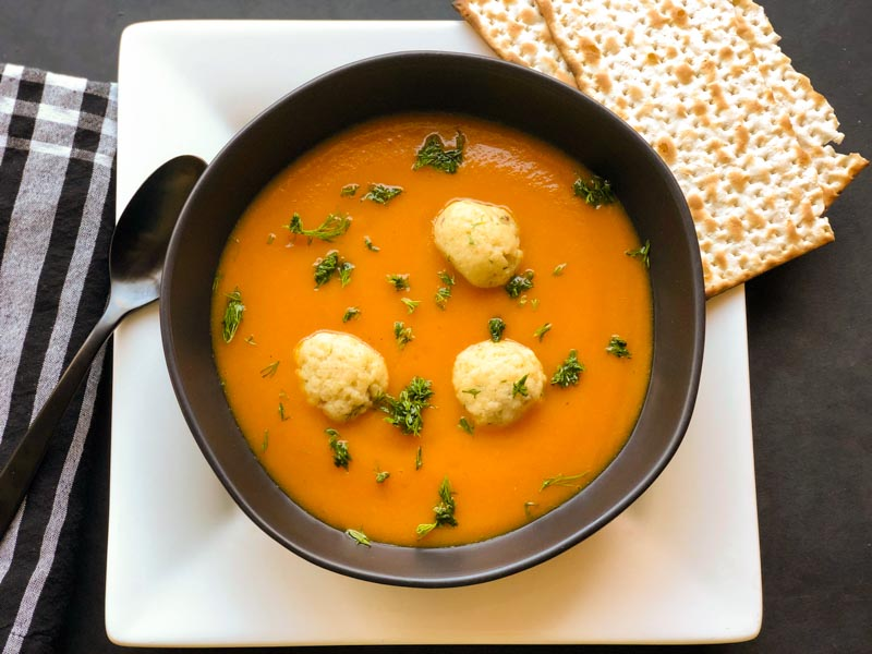 Carrot Squash Sweet Potato Soup in a black bowl, garnished with 3 Mini Dill Matzo Balls. Matzo on the side