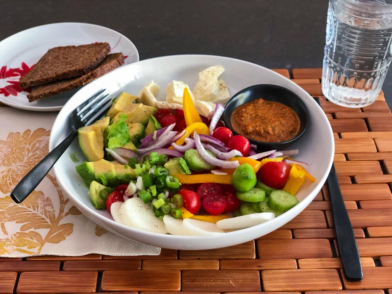 Roasted Red Pepper Pesto served in a small dressing dish inside a single serve salad bowl with an assortment of raw vegetables and healthy brown bread on the side.