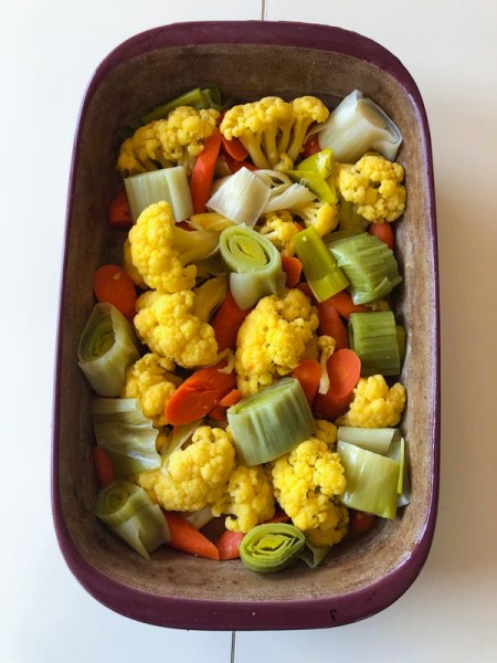 Cooked vegetables in casserole dish, cauliflower, carrots and leeks, cut into chunks