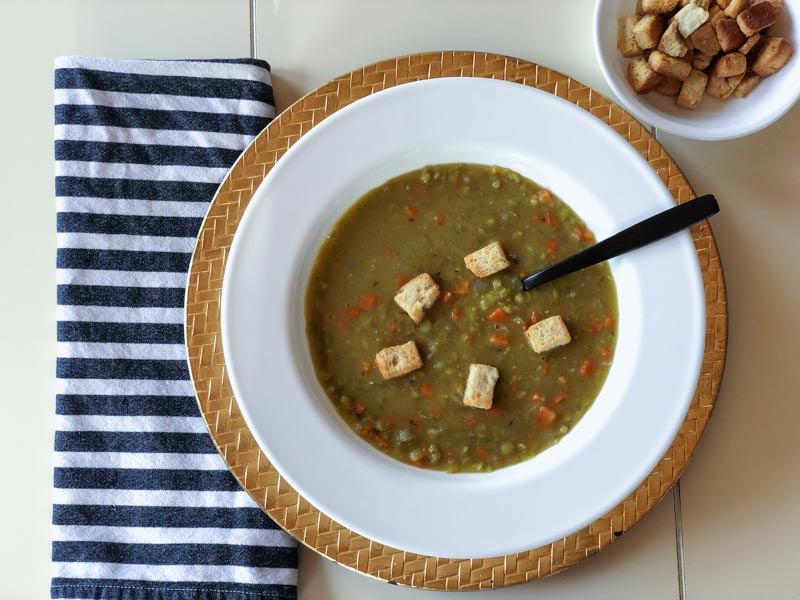 green split pea soup in a bowl with croutons