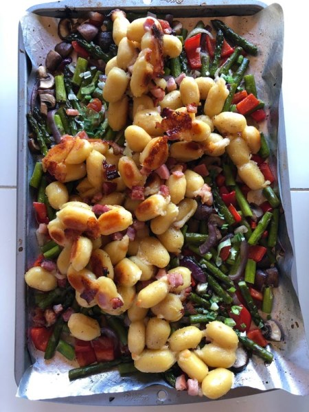 sheet-pan gnocchi tossing cooked vegetables with gnocchi