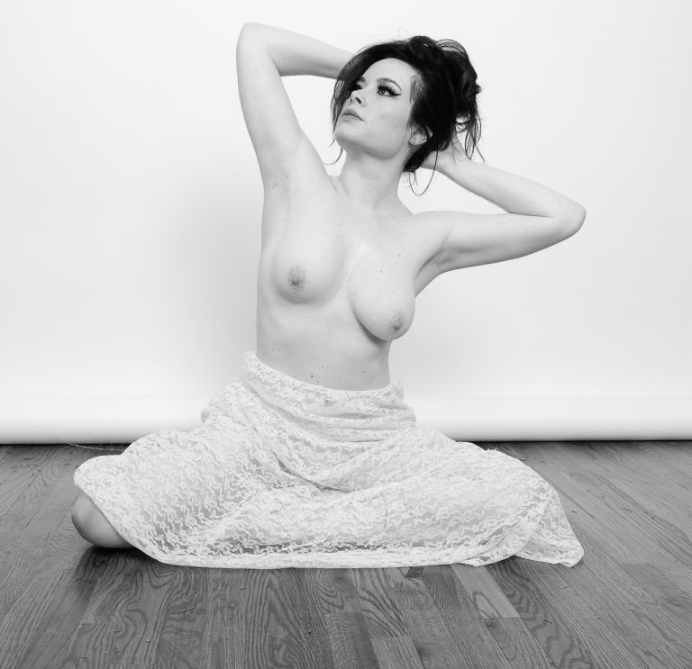Black and White artistic topless photo sitting on the hardwood floor wearing a long lace skirt