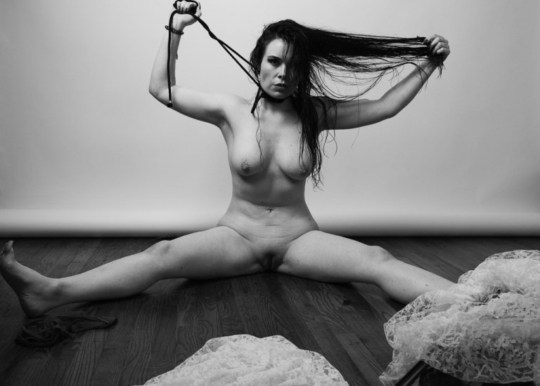 Jasmin Jai sitting on hardwood, legs spread open, fully nude with one hand holding her wet hair and the other pulling up rope from around her neck