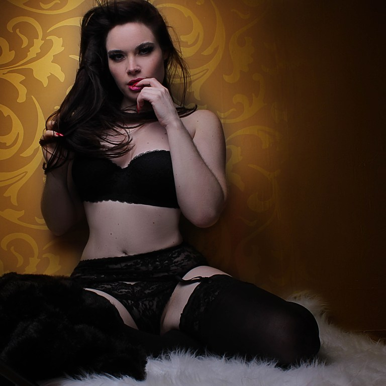 Jasmin Wearing black lingerie sitting on a white rug up against a Gold Wall