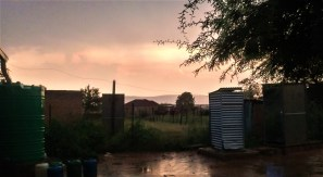 Backyard during a rainstorm. The Jojo are water jugs are on the left and the pit latrines are on the right.