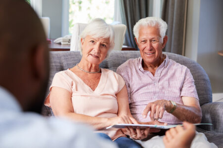Happy senior couple taking financial advice at home