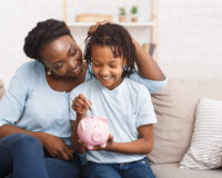 African Mother And Daughter Putting Coins Into Piggy Bank At Home. Free space