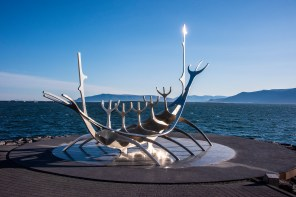 Sun Voyager—Huge 1990 stainless-steel sculpture of a boat by Jón Gunnar Árnason, set on granite beside the sea.