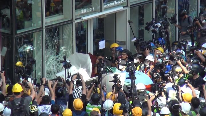 約下午一時半,有示威者開始在立法會的議員入口有衝擊行動。他們用鐵枝、鐵馬及裝有雜物的鐵籠車多次撞向立法會的玻璃幕牆。(影片截圖)
