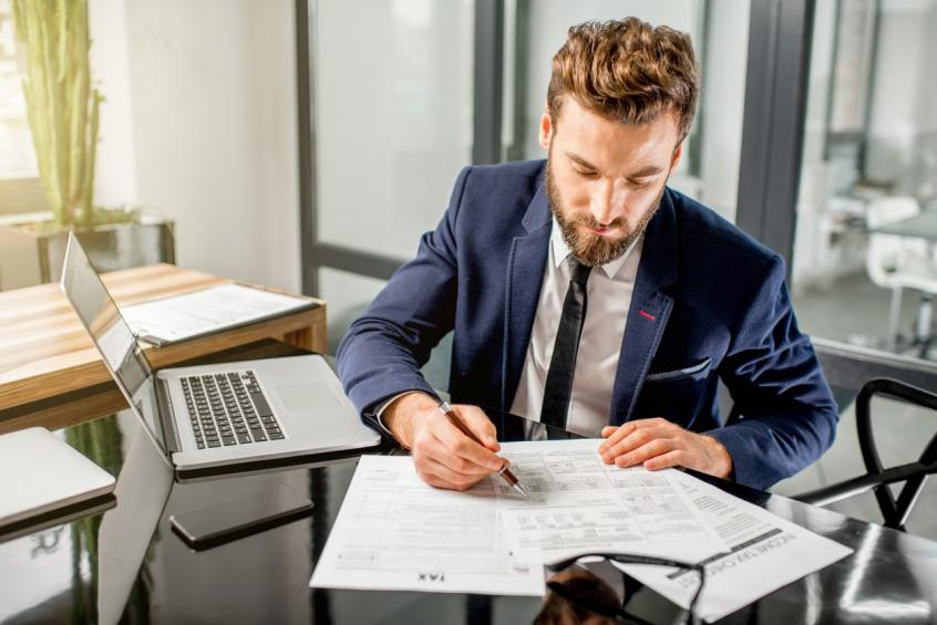 sales ledger manager working at desk with files