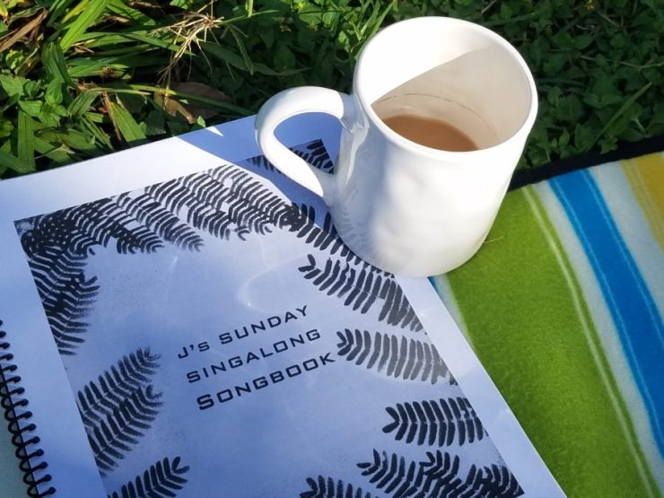 J's Sunday Singalong Songbook w cup of coffee in the sun on the grass