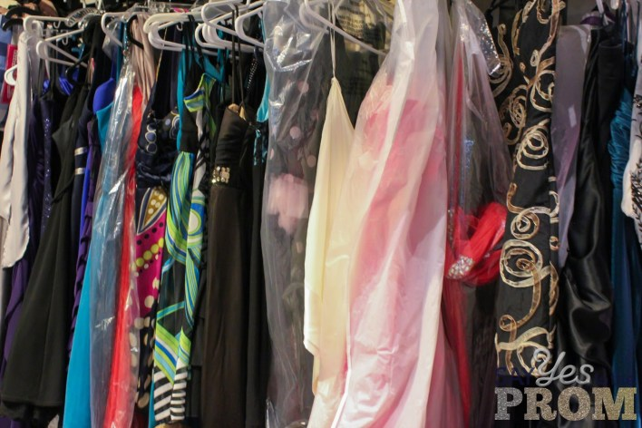 Prom dresses lines up on a rack.