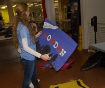"""A committee member holds a """"London"""" sign decorated with glitter."""