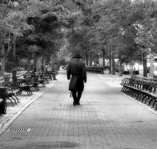 Photo of man walking alone in Riverside Park by Joana Miranda