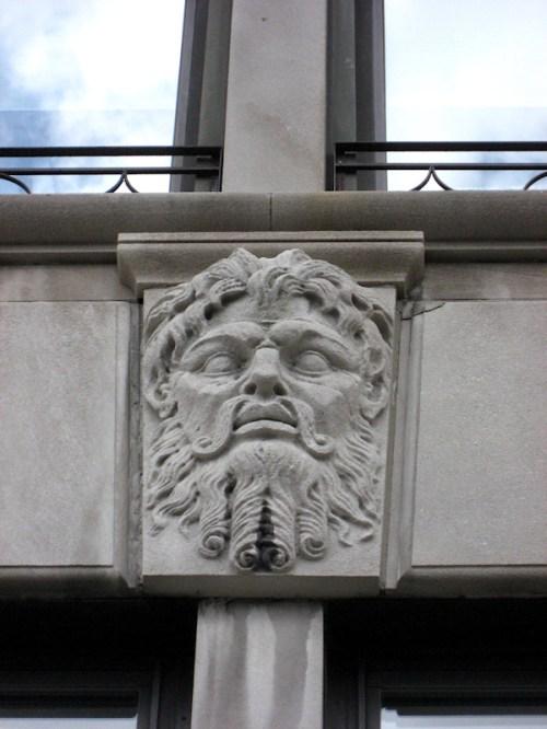 Photo of grouchy-looking male gargoyle on NY City building, taken by Joana Miranda