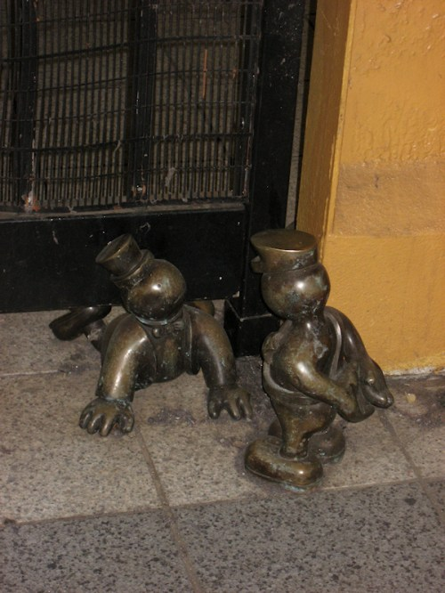 Photo of bronze statues of person trying to sneak into the subway and subway guard, taken by Joana Miranda