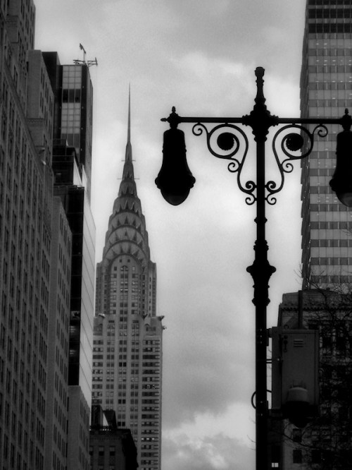 Black and white photo of lamp post and Chrysler building taken by Joana Miranda