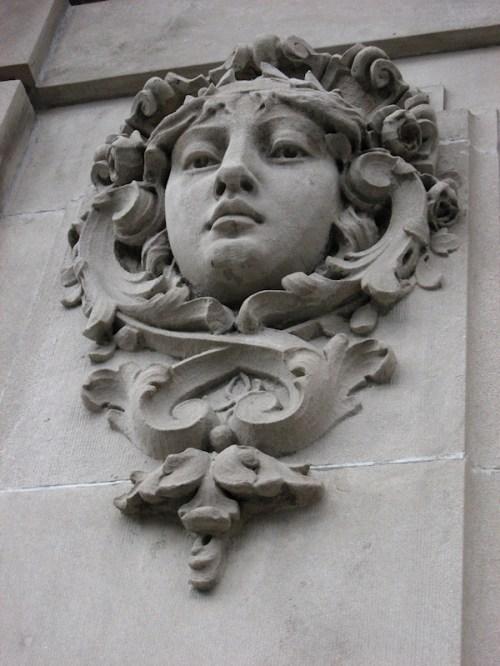 Photo of gentle looking female gargoyle on side of NY City building, taken by Joana Miranda
