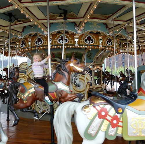 Photo of little girl in pink riding carousel, taken by Joana Miranda