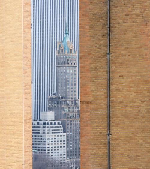 Photo of NYC building seen between two other brick buildings, taken by Joana Miranda