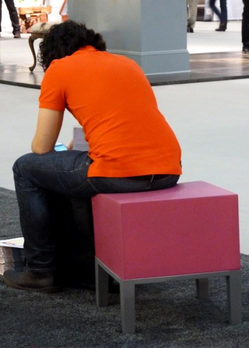 Man in orange shirt sitting on pink stool, photo by Joana Miranda
