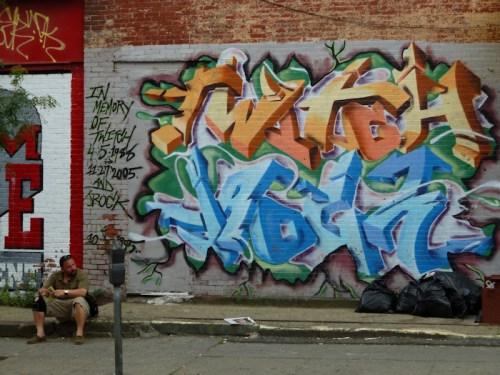 Photo of man sitting in front of wall with graffiti in Williamsburg, Brooklyn, taken by Joana Miranda