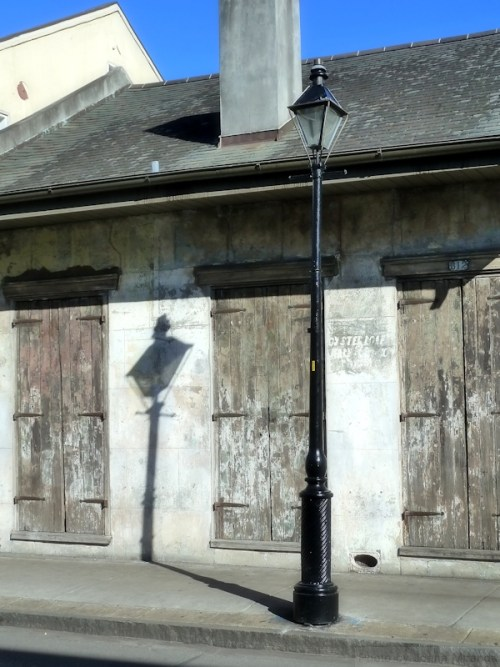 Lantern and shadow against an old grey wall